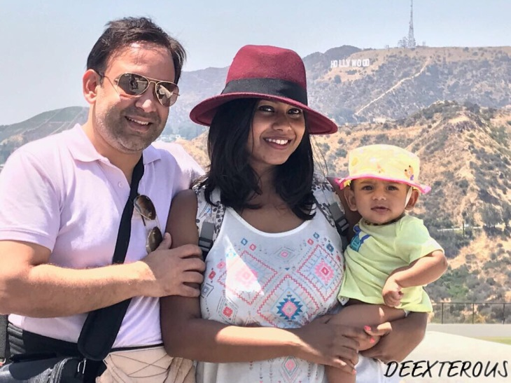 Father, mother and little baby posing in Front of the Hollywood sign in LA.